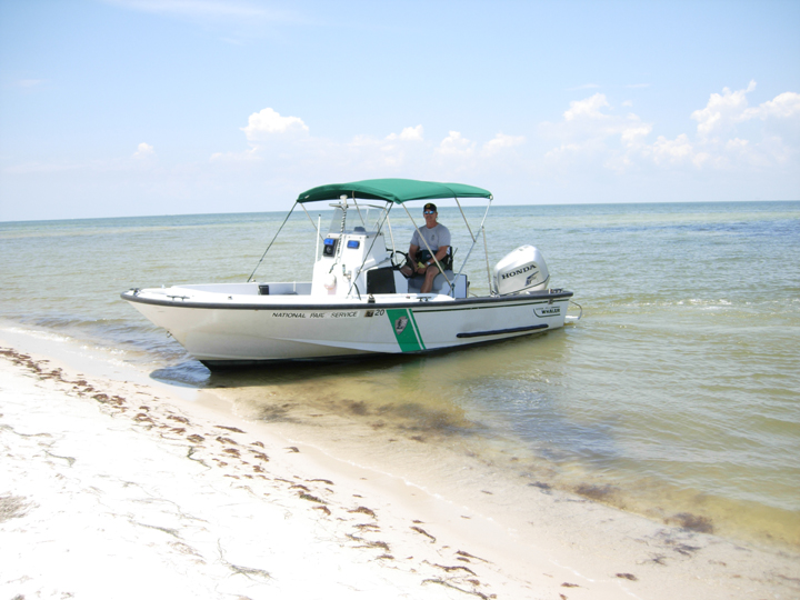 A small boat sits in the shallows right off a sandy white beach.